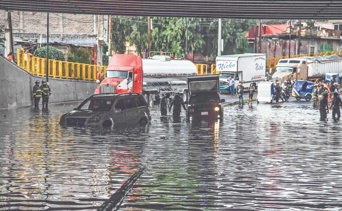 Lluvia causa inundación en bajo puente y deja vehículos varados, en la México-Puebla
