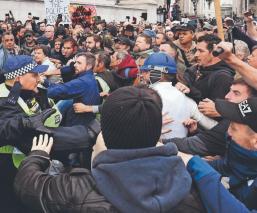 Manifestantes se enfrentan a la policía en protesta anticonfinamiento, en Londres