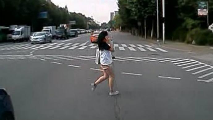 Mujer cruzando la calle con celular